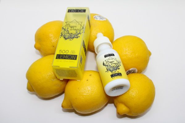 OrganiDrops Lemon bottle and box lying on lemons